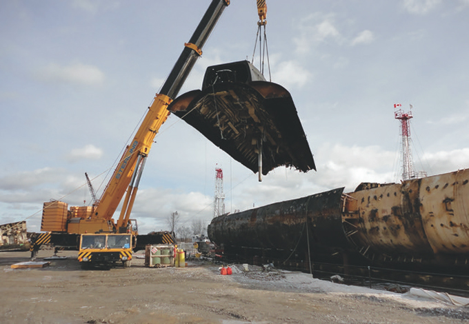 Marine Recycling Corporation removes the top section of a naval submarine during recycling operations.
